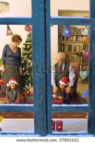 grandparents giving Christmas present to their little granddaughters - stock photo