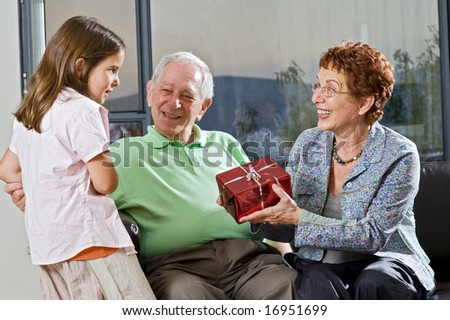 grandparents giving gift to grandchild at home - stock photo