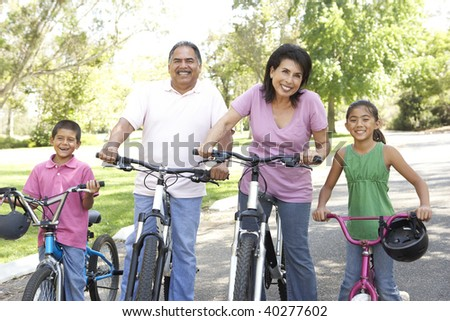 Grandparents In Park With Grandchildren Riding Bikes - stock photo