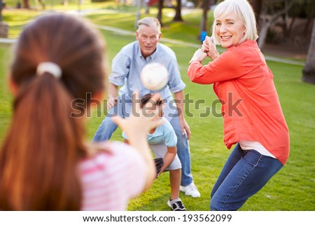 Grandparents Playing Baseball With Grandchildren In Park - stock photo