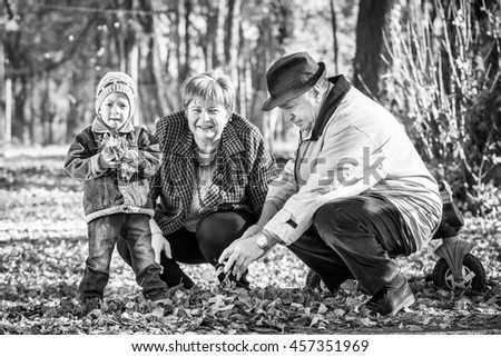 grandparents playing with grandson in a park, black and white photography