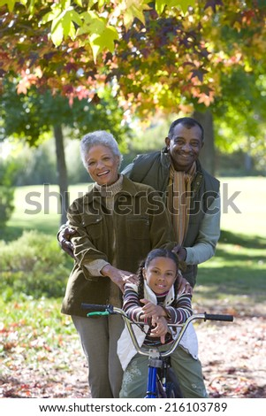 Grandparents posing with granddaughter on bicycle