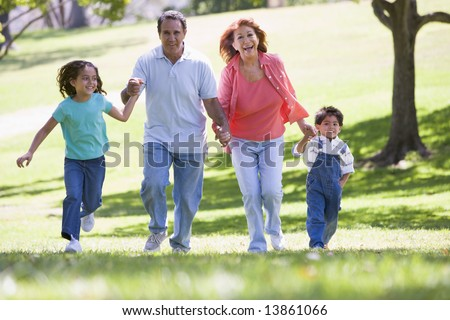 Grandparents running with grandchildren - stock photo