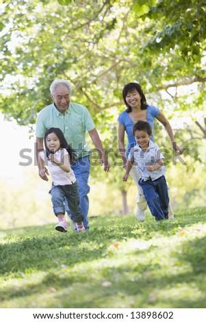 Grandparents running with grandchildren - stock photo