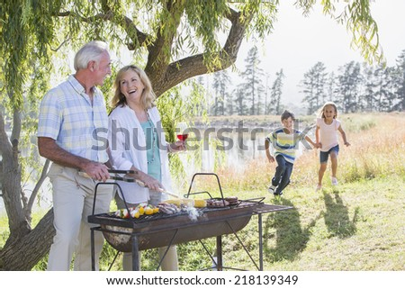 Grandparents Serving Grandchildren At Family Barbeque