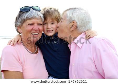 Grandparents showing love to grandchild happy smiling - stock photo