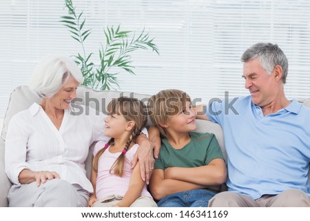 Grandparents speaking with their grandchildren in the living room - stock photo