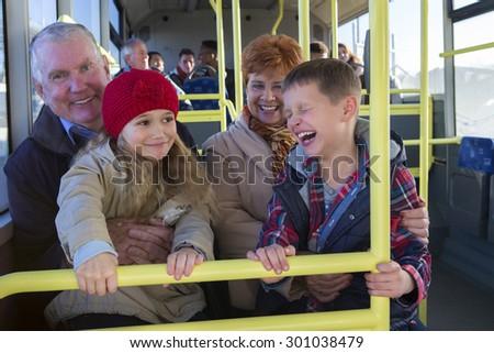 Grandparents taking their grandchildren out via the bus. The children are sitting on their grandparents knees.  - stock photo