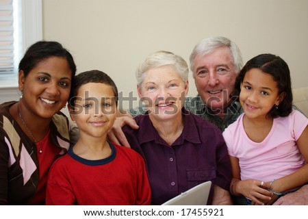 Grandparents together with their family at home - stock photo