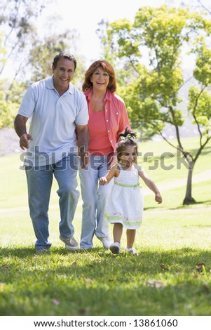 Grandparents walking in park with granddaughter - stock photo