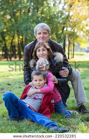 Grandparents walking with grandchildren in the autumn park - stock photo
