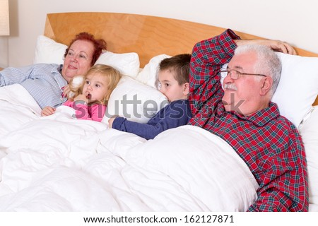 Grandparents watching TV in the bed with their grand kids, they look excited, perhaps its an adventure movie - stock photo