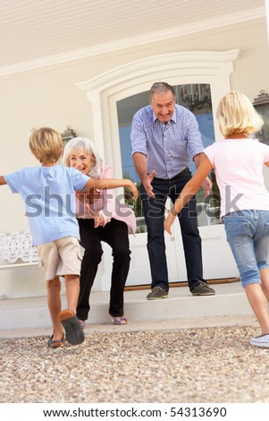 Grandparents Welcoming Grandchildren On Visit To Home - stock photo