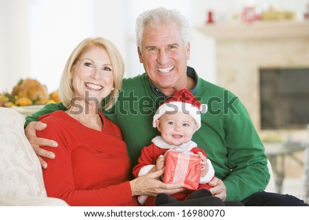 Grandparents With Baby In Santa Outfit - stock photo