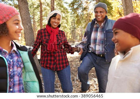 Grandparents With Children Walking Through Fall Woodland