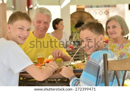 Grandparents with grandchild at breakfast on tropical resort