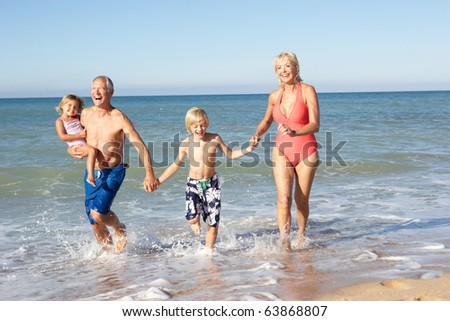 Grandparents With Grandchildren Enjoying Beach Holiday Together