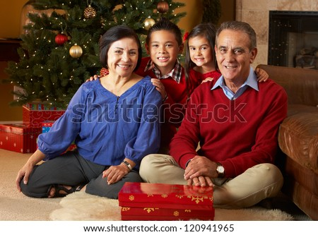 Grandparents With Grandchildren In Front Of Christmas Tree