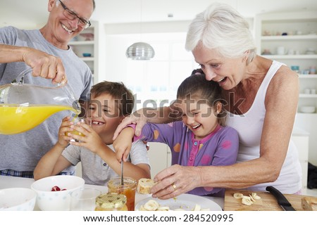 Grandparents With Grandchildren Making Breakfast In Kitchen - stock photo