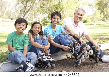 Grandparents With Grandchildren Putting On In Line Skates In Park