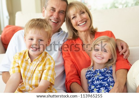 Grandparents With Grandchildren Relaxing On Sofa At Home - stock photo