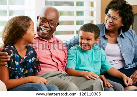 Grandparents With Grandchildren Sitting On Sofa And Talking - stock photo