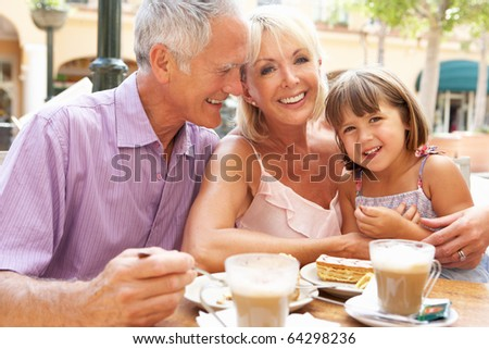 Grandparents With Granddaughter Enjoying Coffee And Cake In Caf? - stock photo