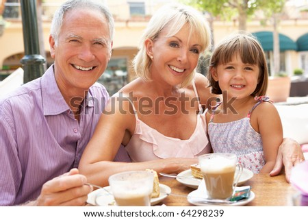 Grandparents With Granddaughter Enjoying Coffee And Cake In Cafe - stock photo