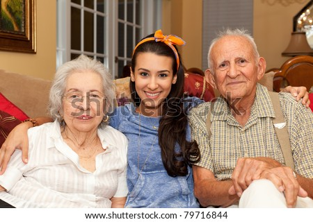 Grandparents with granddaughter in a home setting. - stock photo