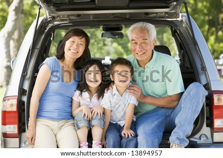 Grandparents with grandkids in tailgate of car - stock photo