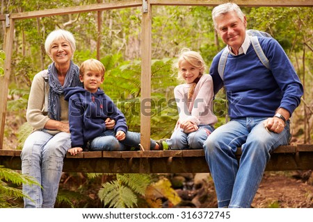 Grandparents with grandkids on bridge in a forest, portrait - stock photo