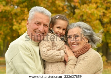 Grandparents with her granddaughter in the autumn park - stock photo