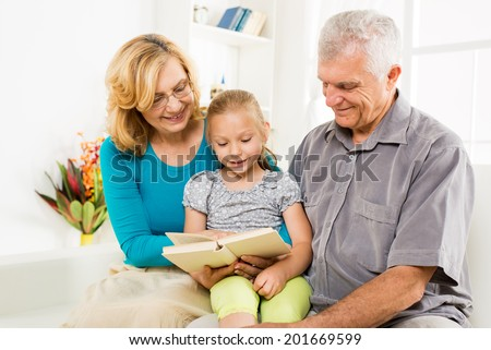 Grandparents with little girl reading book at home - stock photo
