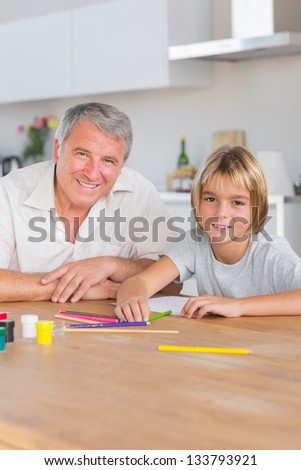 Grandson and grandfather looking at camera with drawings in kitchen - stock photo