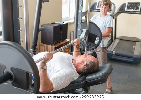 grandson helps his grandfather to lift a barbell - stock photo