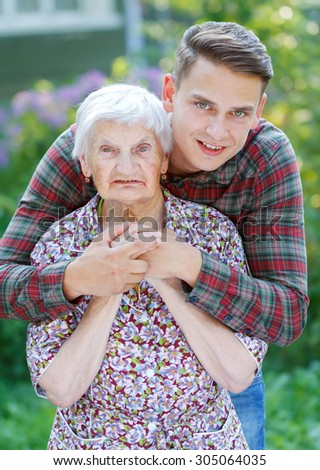Grandson hugging her beautiful  senior wrinkled grandmother - stock photo