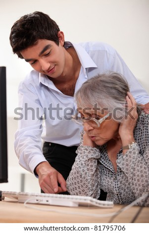 grandson learning his grandmother haw to use a computer - stock photo