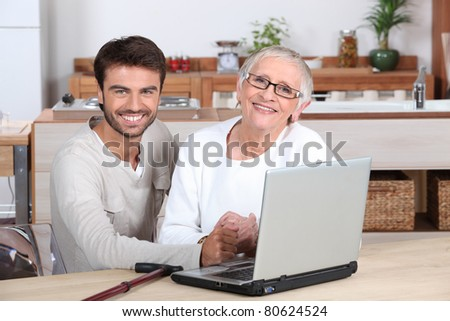 Grandson showing grandmother computer - stock photo