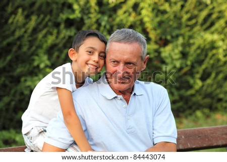 grandson smiling with grandfather in a park - stock photo