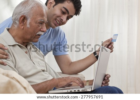 Grandson teaching grandfather how to operate laptop - stock photo