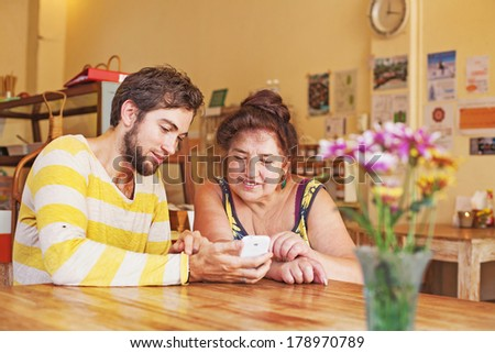 Grandson teaching his grandmother how to use mobile phone - stock photo