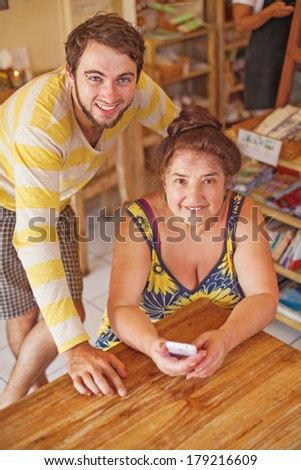 Grandson teaching his grandmother how to use mobile phone (focus on her eyes) - stock photo
