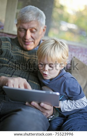Grandson using touchscreen tablet PC with grandfather - stock photo