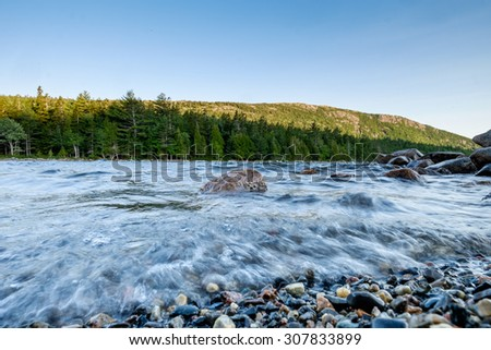 Granite boulders and smaller broken up and smoothed rocks line the shoreline of Jordan Pond in Maine during a windy and rough water day - stock photo