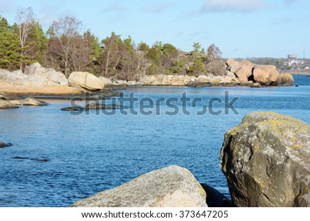 Granite boulders, rocks and some trees in the Swedish shoreline of the Baltic sea. This is outside Karlshamn in February. - stock photo