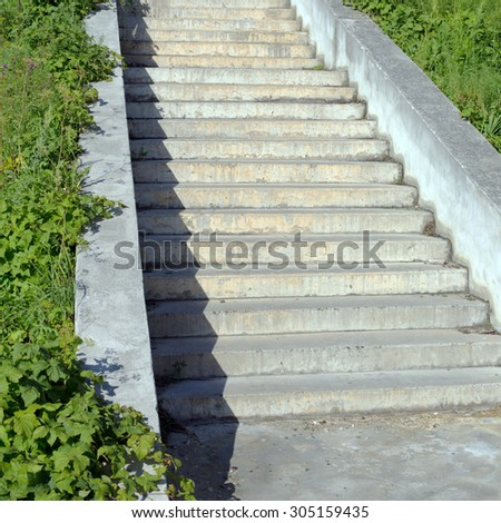 granite or concrete stairs steps and green plant as background under summer sun - stock photo