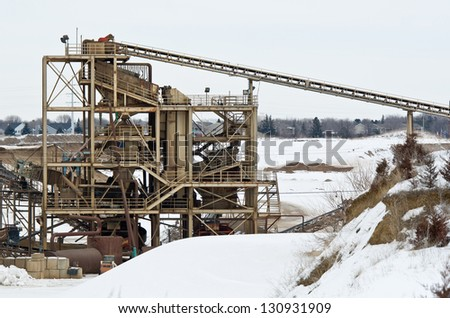 Granite Quarry with Machinery in the Wintertime - stock photo