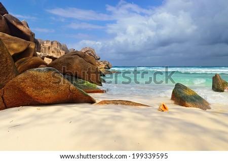 Granite rocky beaches on Seychelles islands, La Digue,Grand Anse. Big orange shell in the surf - stock photo