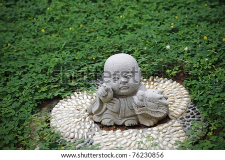 Granite statue of a cute baby monk holding a dragon which is the fifth zodiac sign in the Chinese horoscope in a green park.
