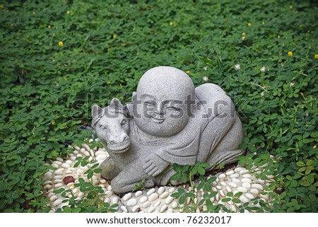 Granite statue of a cute baby monk riding a horse which is the seventh animal zodiac sign in the Chinese horoscope in a green park. - stock photo